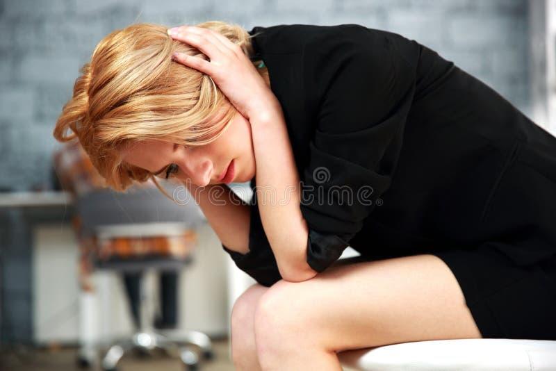 Mulher que senta-se na cadeira do escritório que toca em sua cabeça imagem de stock royalty free