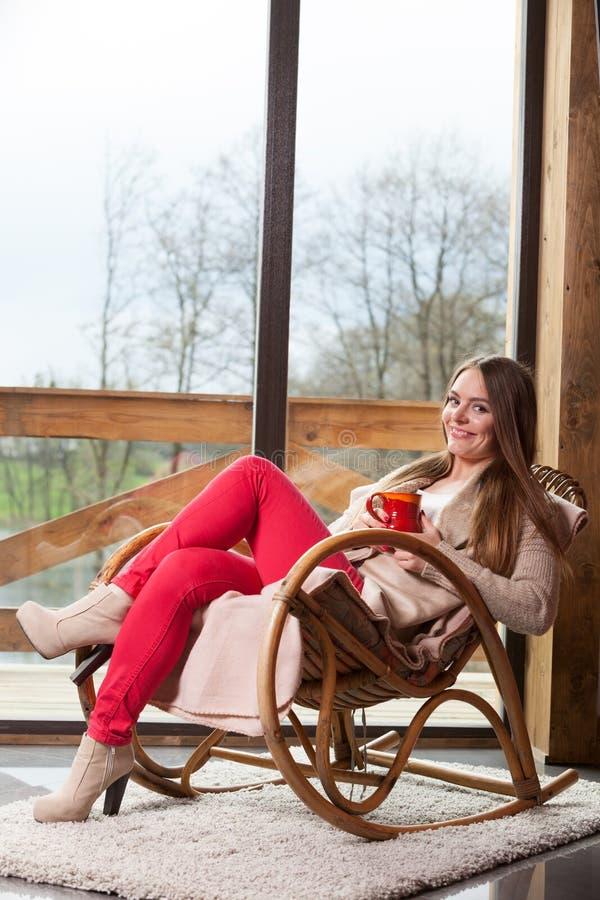 Mulher que senta-se na cadeira que relaxa em casa fotos de stock royalty free