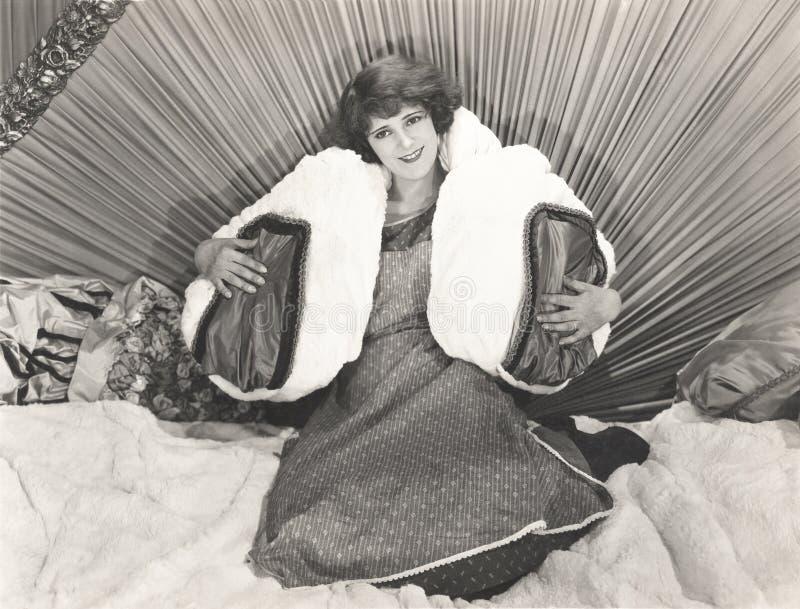 Mulher que senta-se na cama com descansos foto de stock