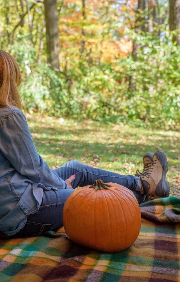 Mulher que senta-se na cobertura do piquenique com a abóbora no outono fotografia de stock royalty free