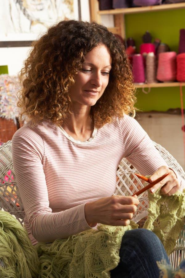 Mulher que senta-se na confecção de malhas da cadeira imagem de stock