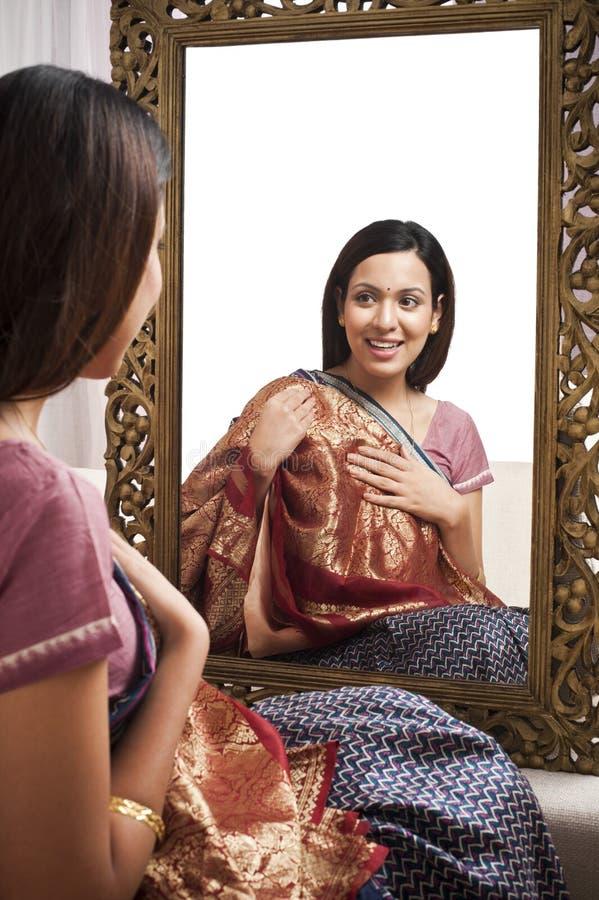 Mulher que senta-se na frente do espelho imagens de stock royalty free