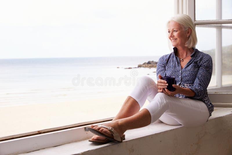 Mulher que senta-se na janela e que olha a opinião bonita da praia imagem de stock