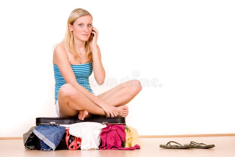 Mulher que senta-se na mala de viagem fotos de stock