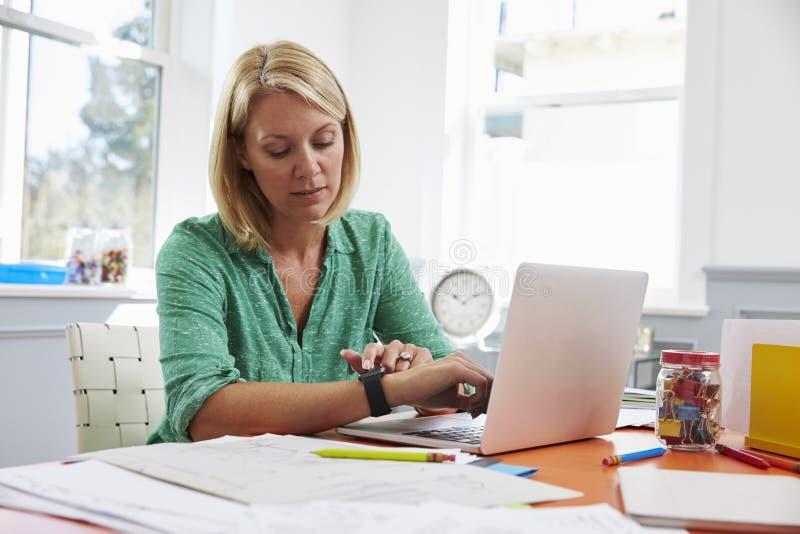 Mulher que senta-se na mesa no escritório domiciliário que olha o relógio esperto imagens de stock royalty free