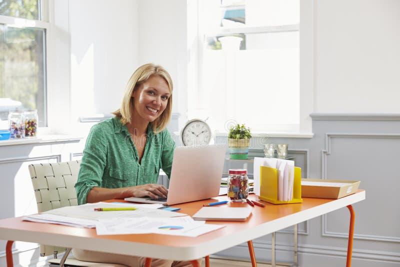 Mulher que senta-se na mesa que trabalha no portátil no escritório domiciliário foto de stock