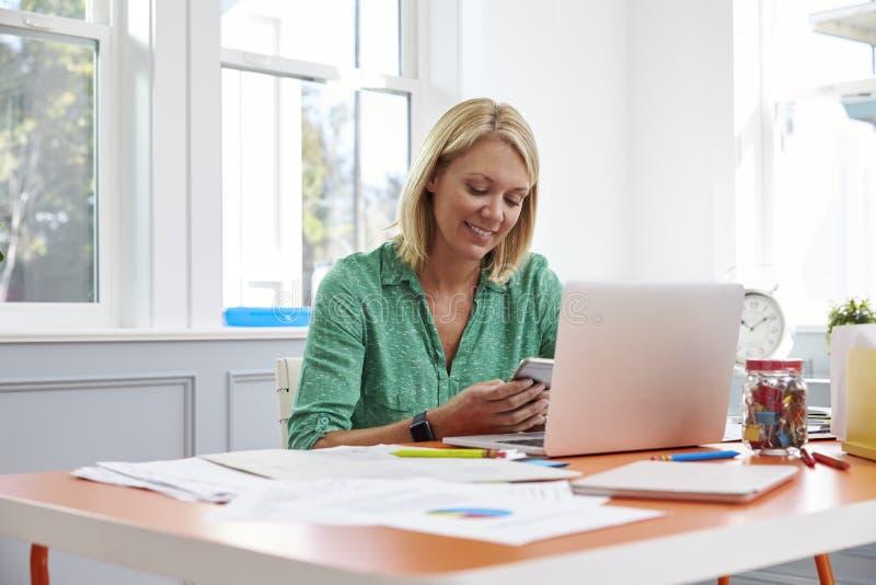 Mulher que senta-se na mesa usando o telefone celular no escritório domiciliário foto de stock royalty free