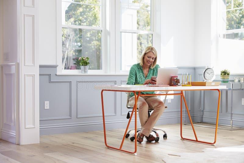 Mulher que senta-se na mesa usando o telefone celular no escritório domiciliário fotografia de stock
