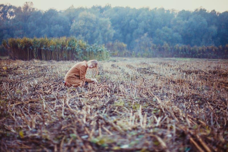 Mulher que senta-se na paisagem triste no campo foto de stock