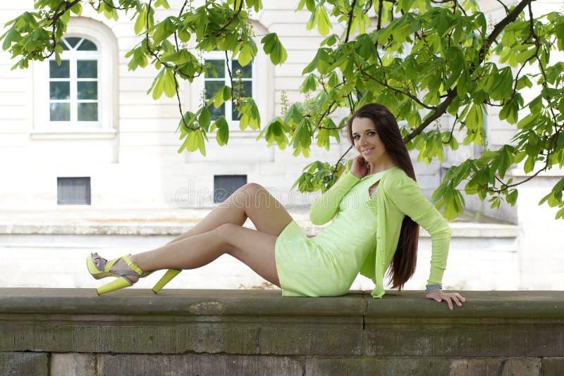 Mulher que senta-se na parede de pedra fotografia de stock