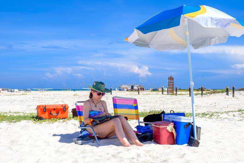 Mulher que senta-se na praia imagem de stock royalty free