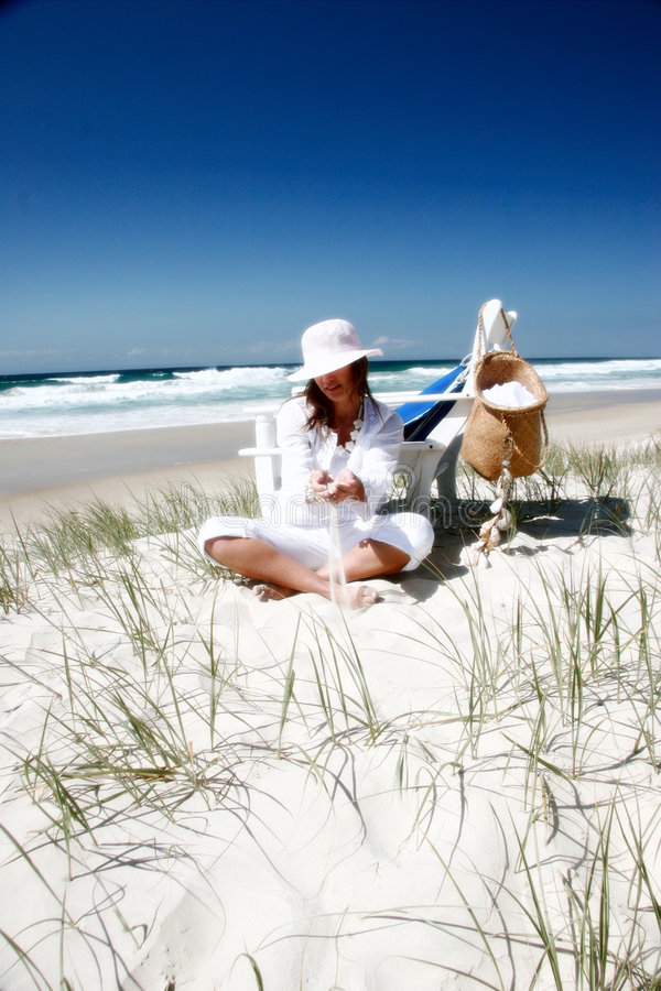 Mulher que senta-se na praia imagem de stock