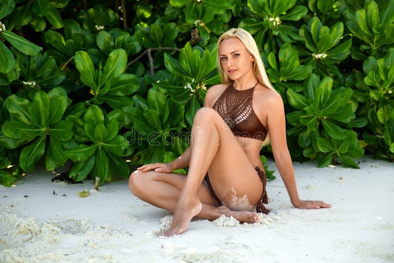 Mulher que senta-se na praia branca da areia do ` s de Zanzibar fotos de stock royalty free