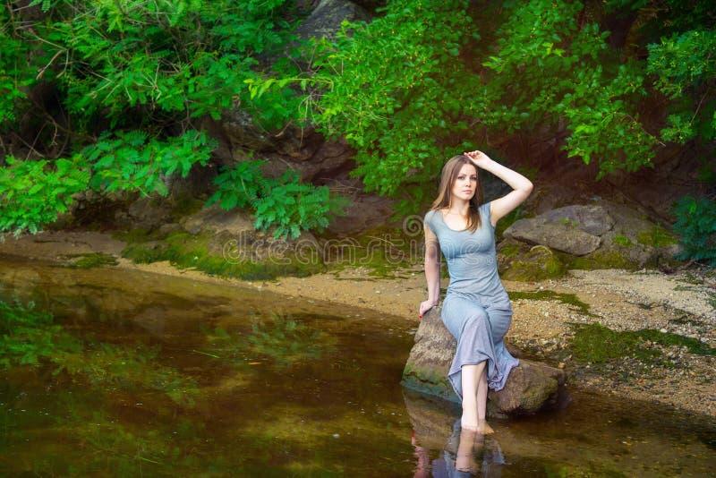 Mulher que senta-se na rocha em uma lagoa imagem de stock