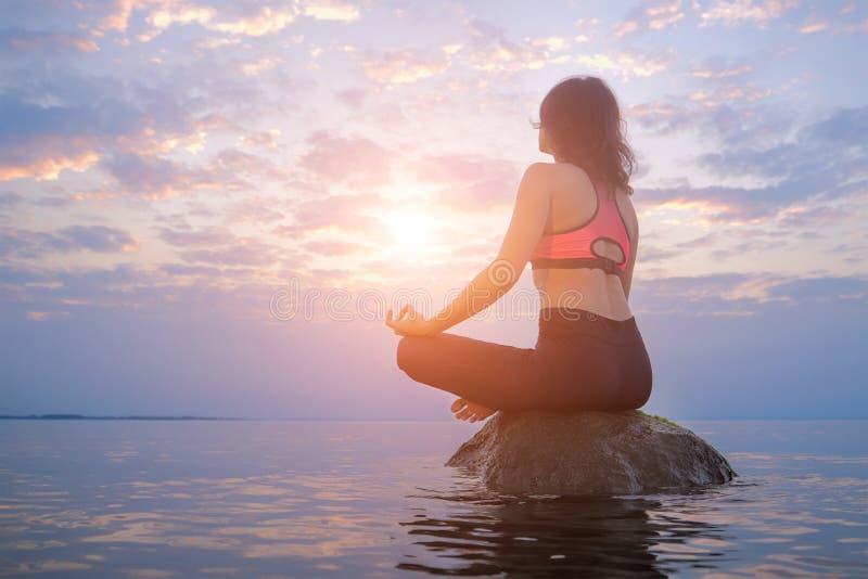 Mulher que senta-se na rocha no mar Conceito meditando e de relaxamento imagens de stock royalty free