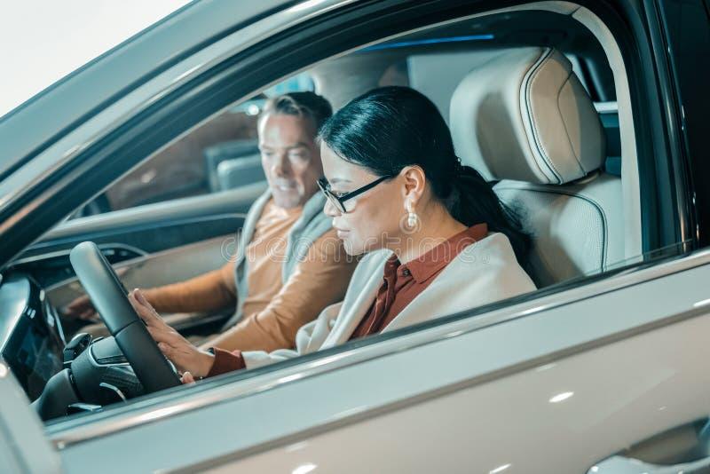 Mulher que senta-se na roda de um carro novo imagens de stock royalty free