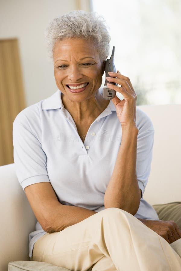 Mulher que senta-se na sala de visitas usando o telefone imagens de stock royalty free