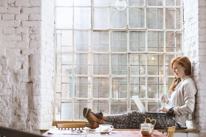 Mulher que senta-se na soleira com caderno imagens de stock