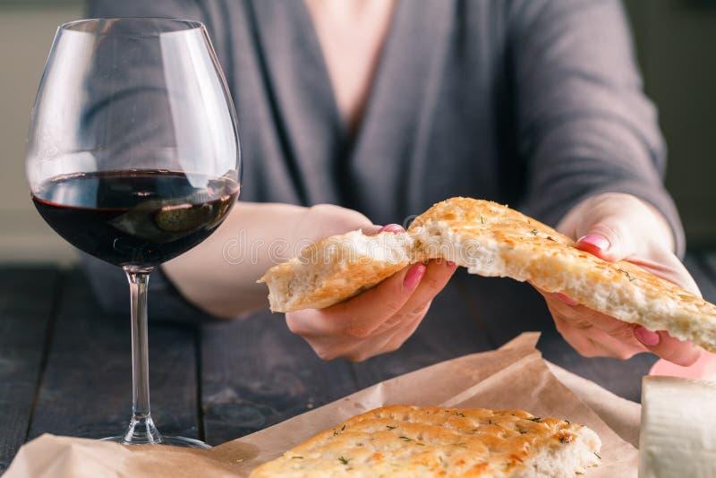 A mulher que senta-se na tabela aprecia um grânulo e um vidro do vinho tinto fotos de stock royalty free