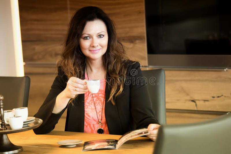Mulher que senta-se na tabela e que lê o compartimento fotos de stock