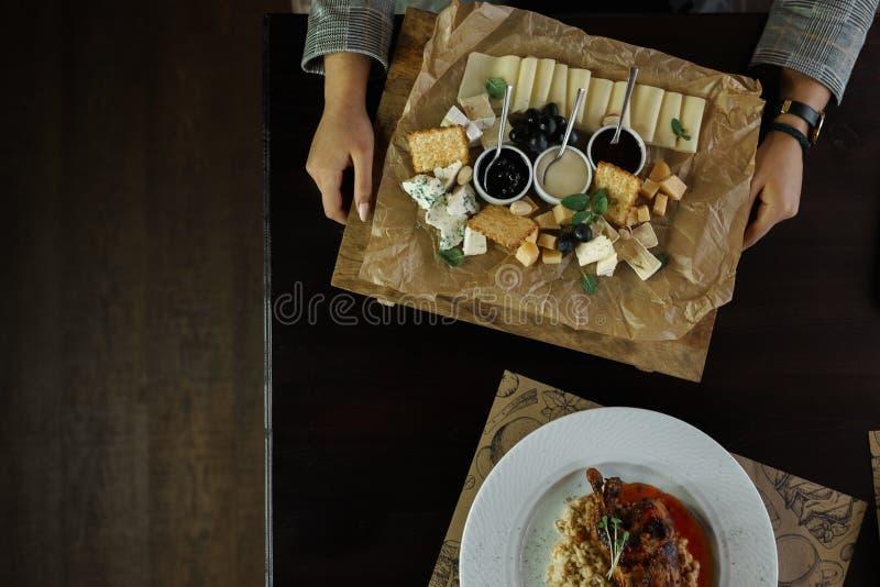 Mulher que senta-se na tabela que guarda uma placa com grupo de queijo, queijo de Gouda, feta, queijo azul com mel doce fotos de stock royalty free
