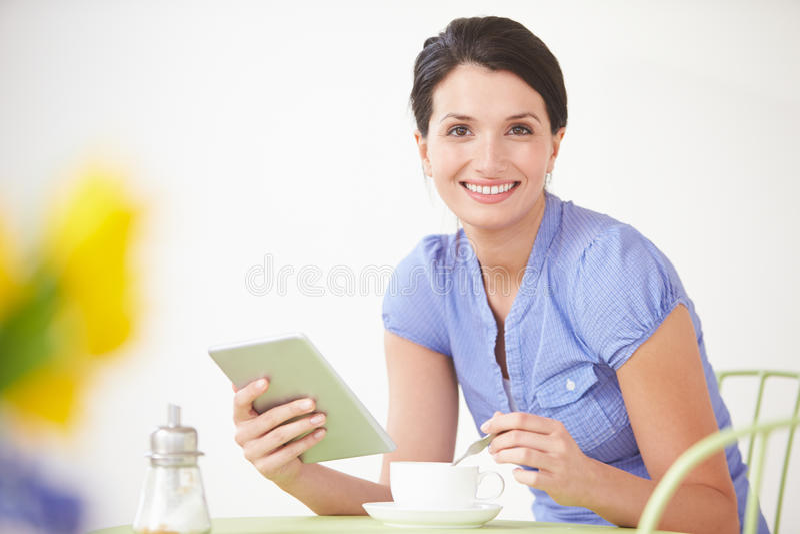 Mulher que senta-se na tabela usando a tabuleta de Digitas fotos de stock royalty free