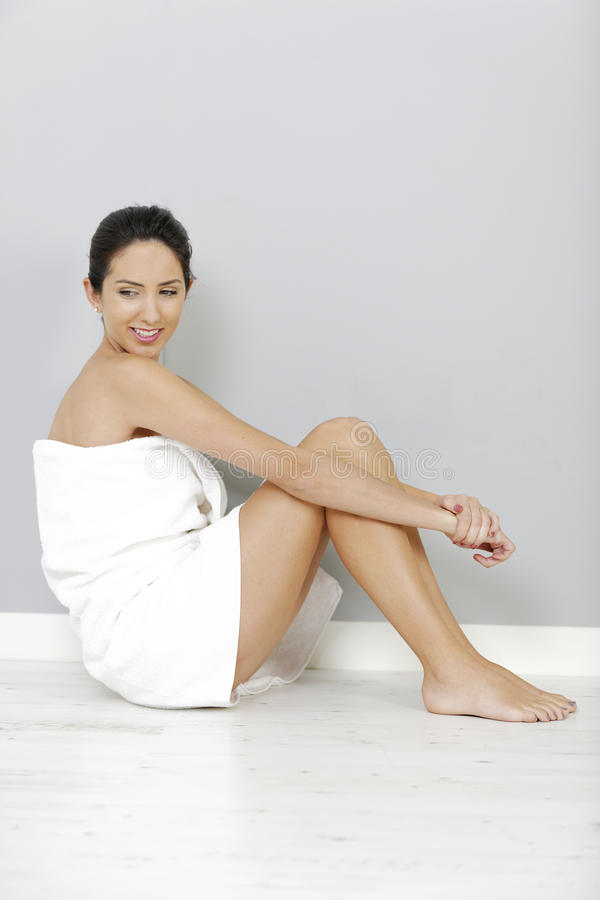 Mulher que senta-se na toalha de banho imagem de stock royalty free