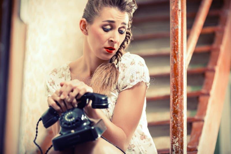 Mulher que senta-se nas escadas e que espera uma chamada fotos de stock royalty free