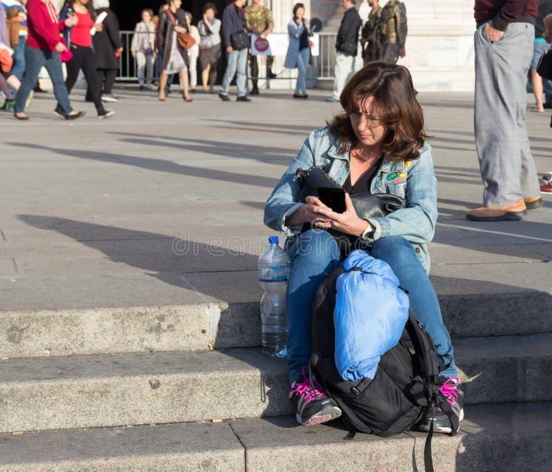 Mulher que senta-se nas escadas que leem uma mensagem no telefone celular imagens de stock