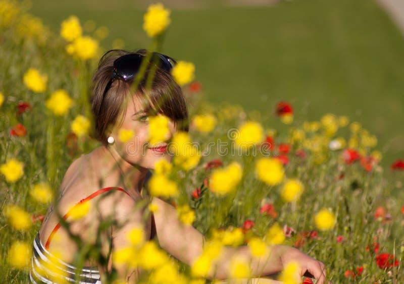 Mulher que senta-se nas flores fotografia de stock