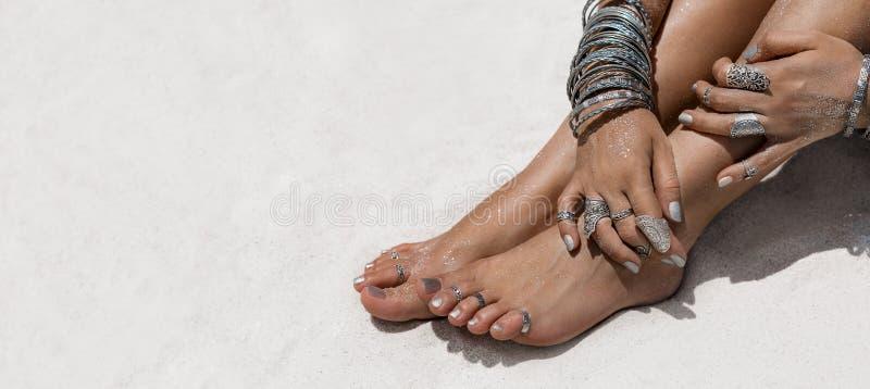 Mulher que senta-se nas mãos e nos pés da areia com accessori étnico imagens de stock royalty free