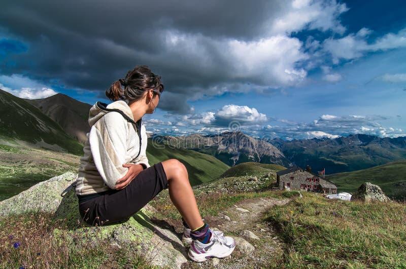 A mulher que senta-se nas montanhas observou uma cabana alpina e o vi foto de stock royalty free