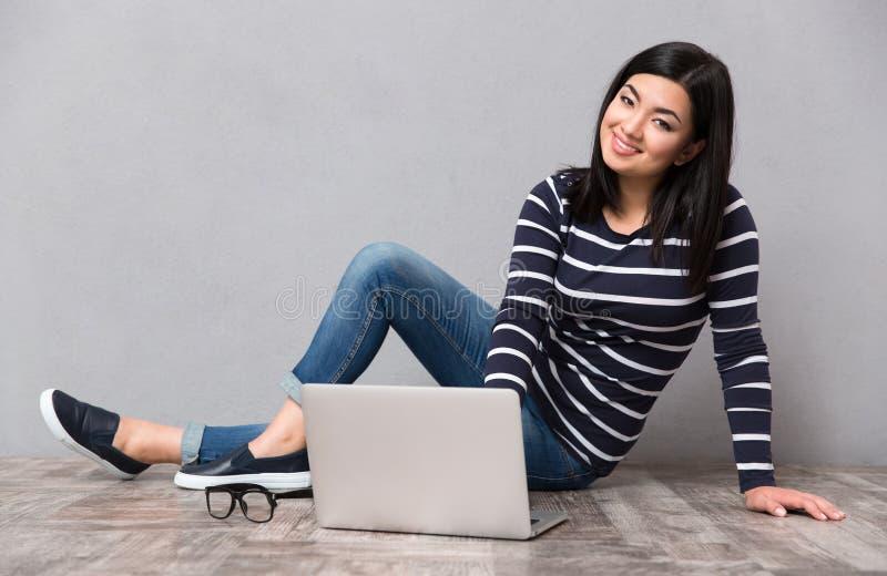 Mulher que senta-se no assoalho com portátil fotografia de stock royalty free