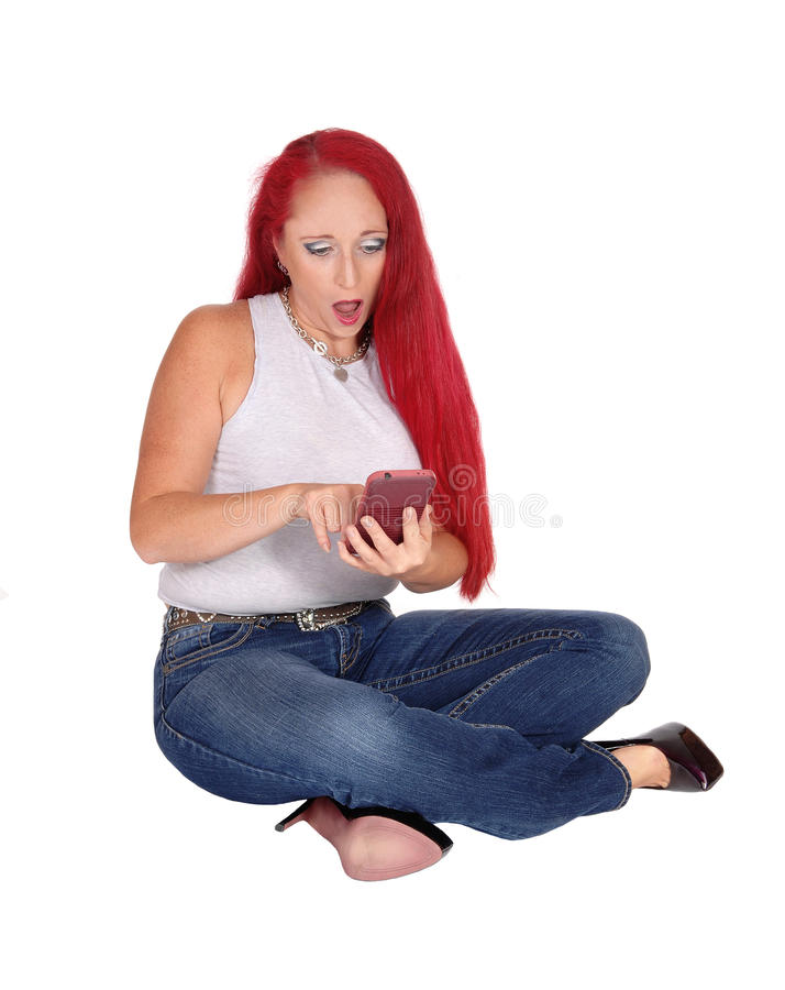 Mulher que senta-se no assoalho com telefone celular fotografia de stock royalty free