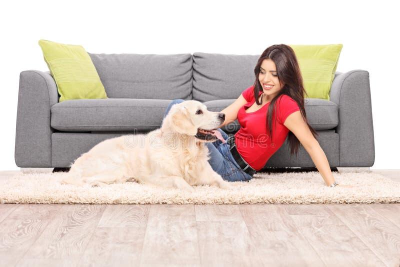Mulher que senta-se no assoalho com um cão fotografia de stock royalty free