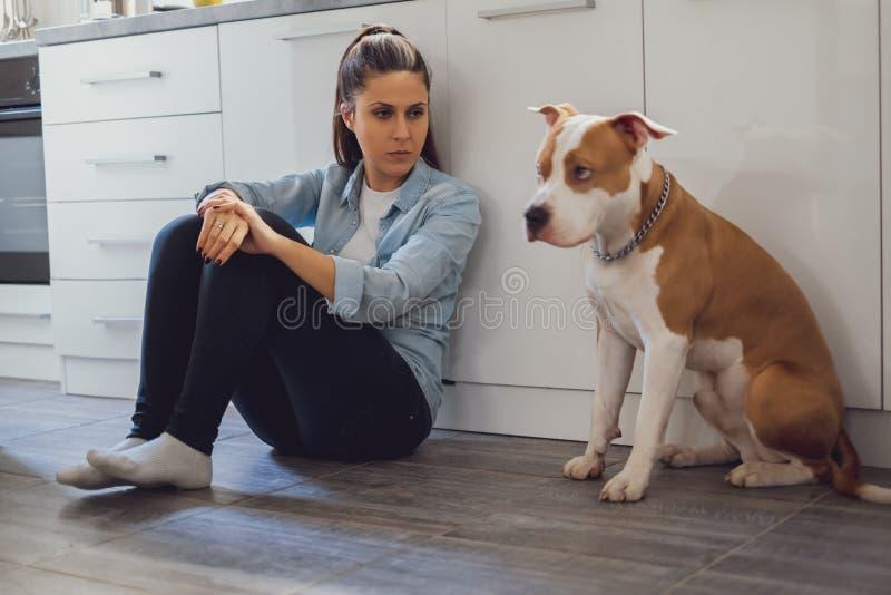 Mulher que senta-se no assoalho da cozinha louco em seu cão fotografia de stock
