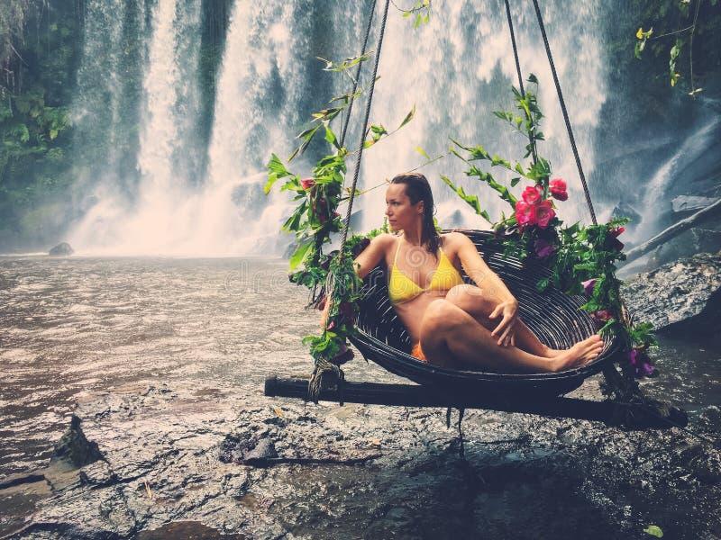 Mulher que senta-se no balanço florescido perto da cachoeira, Phnom Koulen em Siem Reap, Camboja foto de stock