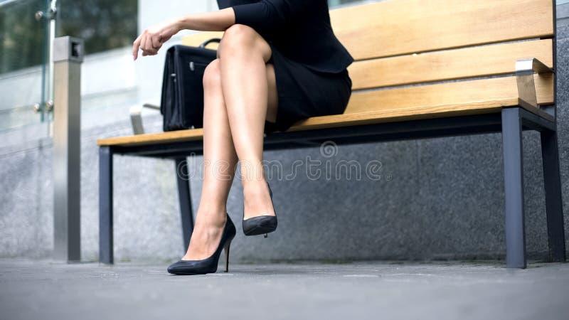 Mulher que senta-se no banco, cansado do passeio em sapatas alto-colocadas saltos incômodas imagem de stock