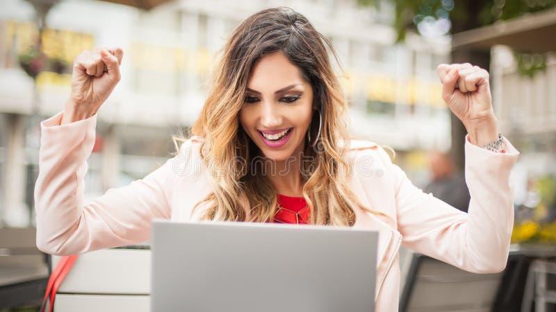 Mulher que senta-se no café, parte dianteira do portátil que levanta suas mãos imagens de stock
