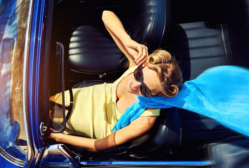Mulher que senta-se no carro retro foto de stock royalty free