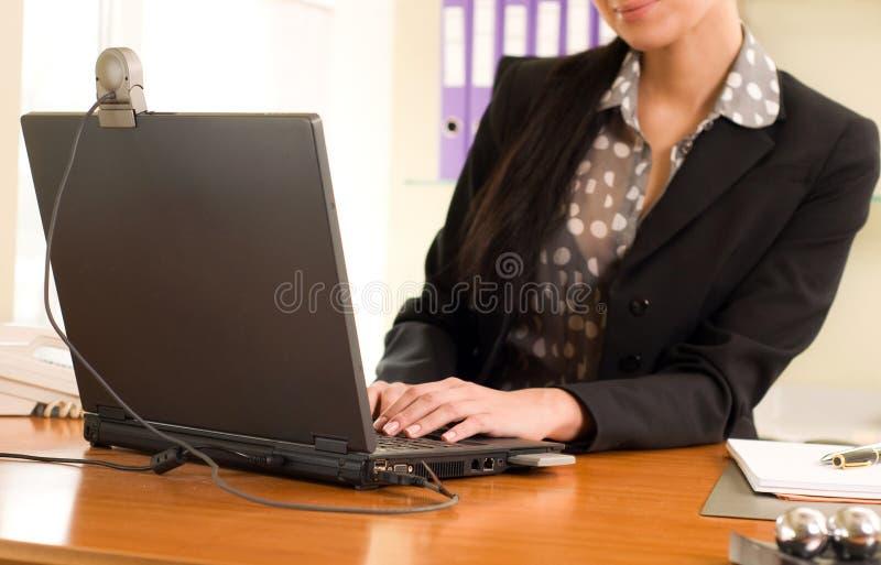 Mulher que senta-se no escritório na frente do portátil fotos de stock royalty free