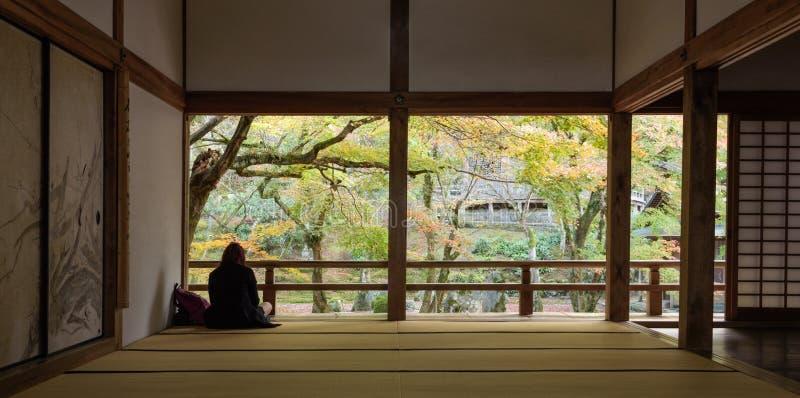 Mulher que senta-se no jardim de rocha da parte traseira do templo do komyozenji imagem de stock
