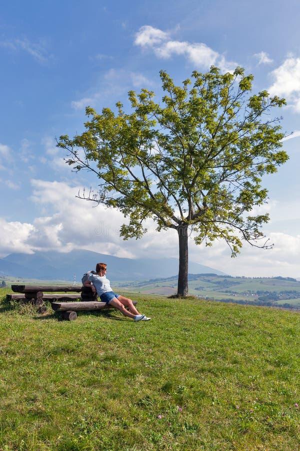 Mulher que senta-se no monte do verão perto de Liptovsky Trnovec, Eslováquia imagens de stock royalty free