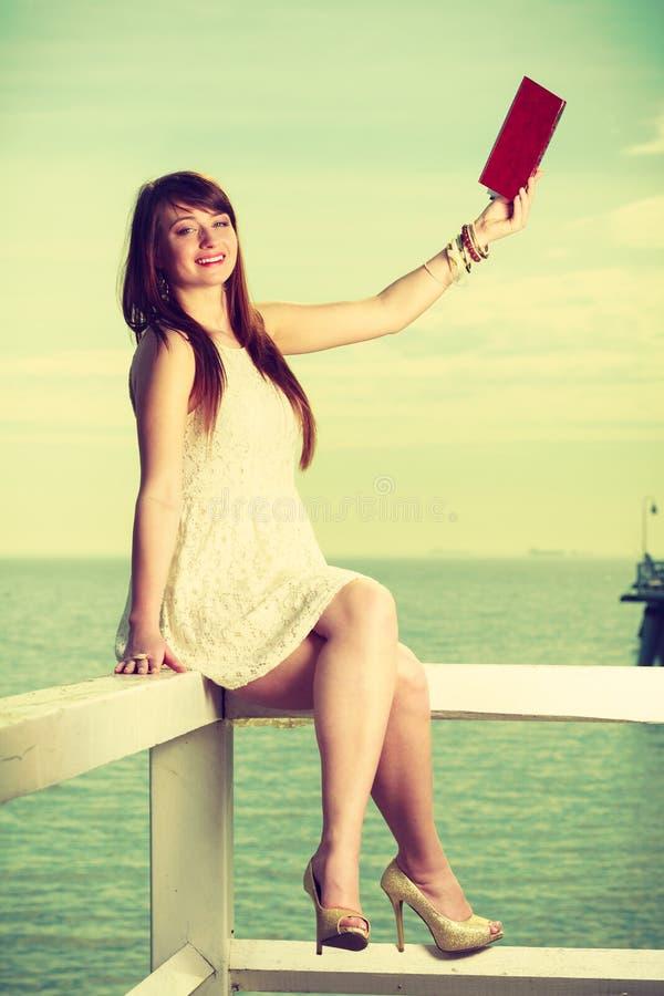 Mulher que senta-se no obstáculo perto do mar, livro de leitura imagem de stock royalty free