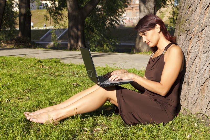 Mulher que senta-se no parque com um portátil fotos de stock royalty free