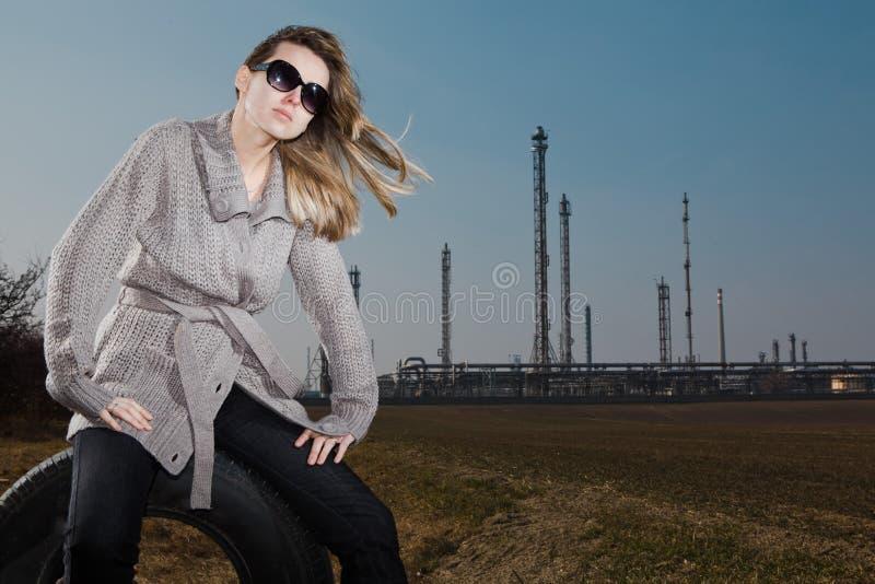Mulher que senta-se no pneu usado - a pele natural sem retoca fotos de stock royalty free