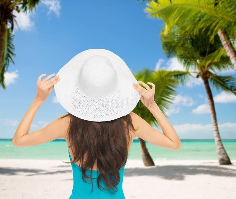 Mulher que senta-se no roupa de banho com chapéu imagem de stock royalty free
