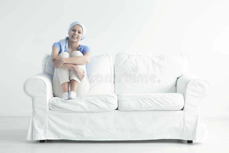 Mulher que senta-se no sofá fotos de stock royalty free
