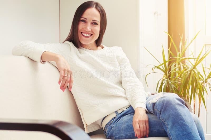 Mulher que senta-se no sofá foto de stock