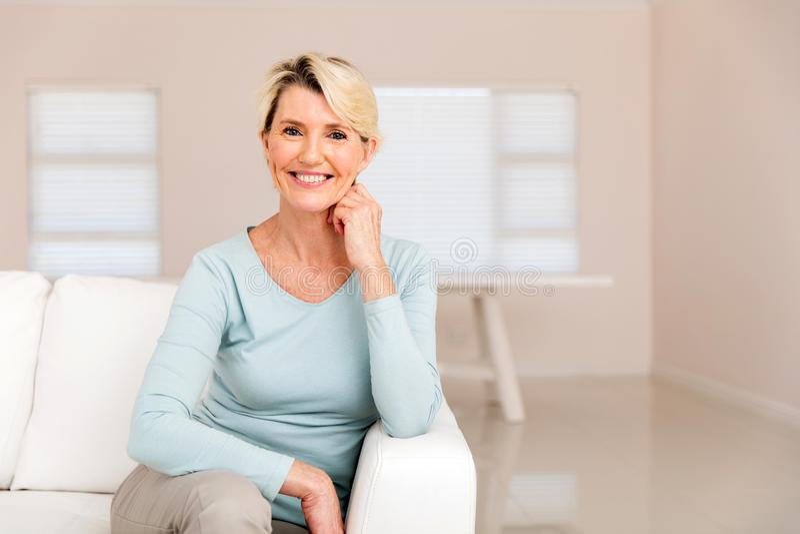 Mulher que senta-se no sofá fotografia de stock